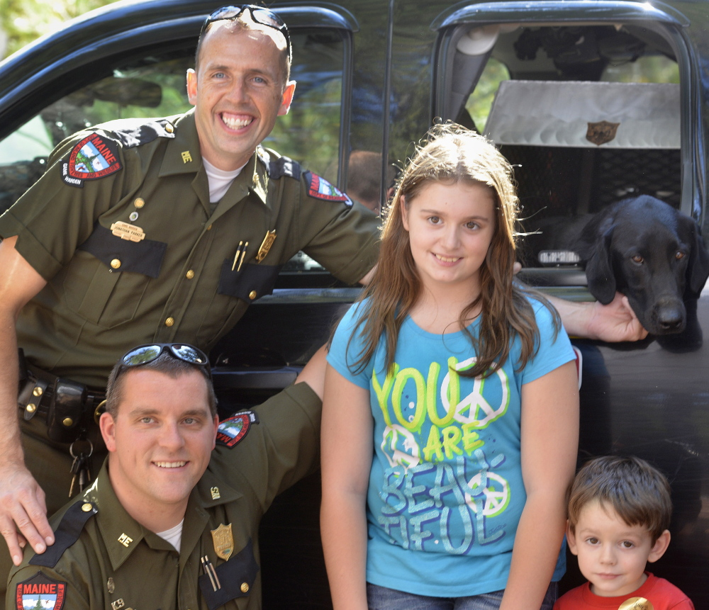 Wardens Jonathan Parker and Alan Curtis and their faithful dog, Sig, pose with fans Kaitlyn Clark, 11, and her 3-year-old brother, Dylan, from Lyman.