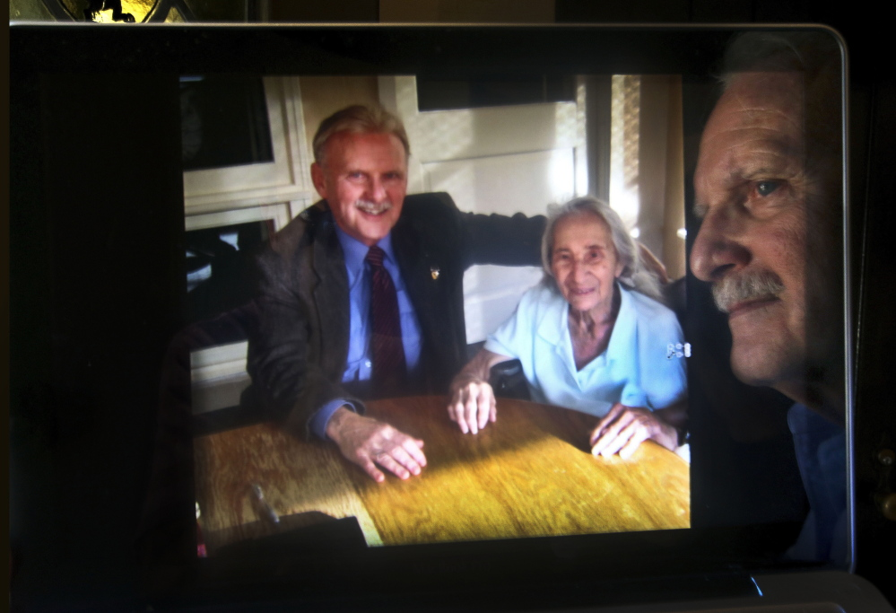 James Caccavo is reflected in his computer screen, next to a photograph of him with his elderly neighbor Sarah Cheiker, taken in 2012 at a health care center in Fryeburg, Maine, where she is currently living. Cheiker, now 89, disappeared in 2008 from her home in Los Angeles that was later bulldozed and replaced by a bigger house.