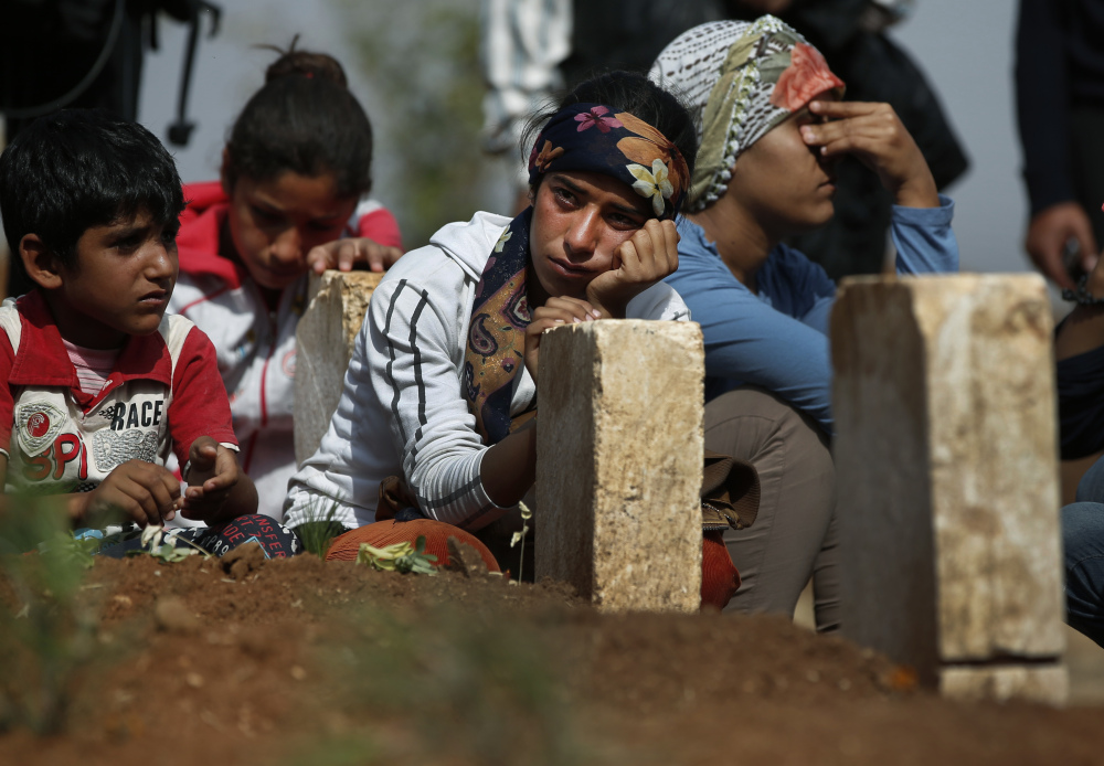 Kurdish people sit by the grave as they mourn their loved one, a Kurdish fighter, name not given, who was killed in the fighting with the militants of the Islamic State group in Kobani, Syria, and was buried at a cemetery in Suruc, on the Turkey-Syria border.