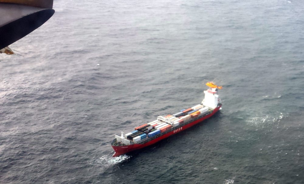 A Canadian Coast Guard helicopter flies near a Russian container ship, carrying hundreds of tons of fuel drifts without power in rough seas off British Columbia's northern coast on Friday.