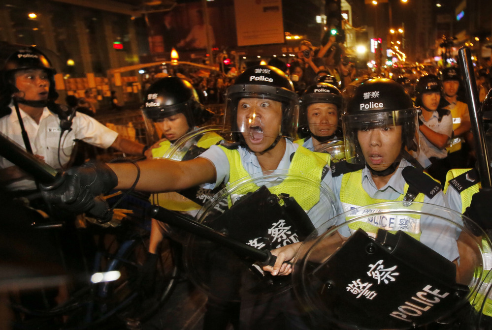 Riot police officers advance on a pro-democracy protest encampment in the Mong Kok district of Hong Kong on Saturday. The neighborhood is a flashpoint for protests.