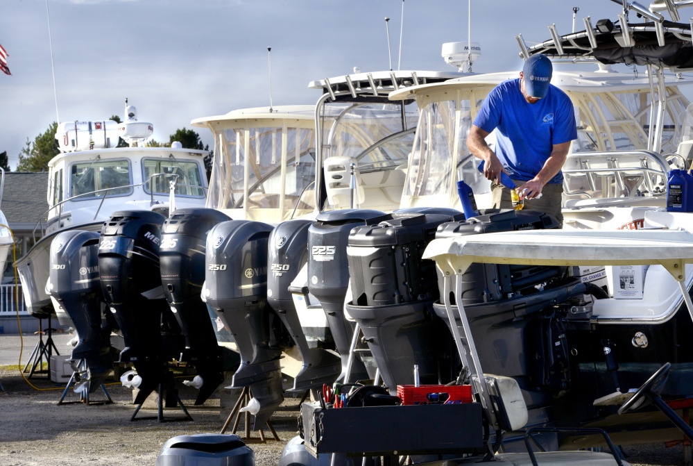 """Marine mechanic Frank Didonato works on motors last week at Port Harbor Marine in South Portland. Didonato has been working at the yard for more than four years. """"I like being on the water where every day is different,"""" he said."""