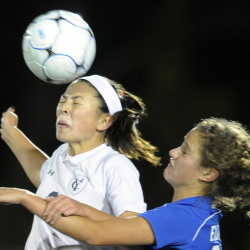 Yarmouth's Lane Simsarian, left, connects with the ball for a header as she fends off Marcy Kittredge during a girls soccer game in Yarmouth Monday. Gabe Souza / Staff Photographer