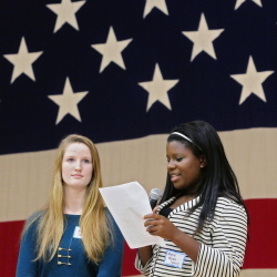 Greater Portland Christian School student Jess Smith, left, and Kyrie Austin read out results during the mock election rally-and-tally event Wednesday at the Augusta Armory.