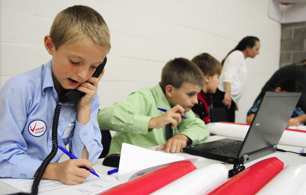 Fort Fairfield Elementary School students Alex Oakes, left, 11, and Chase Coiley, 10, take a turn working at the results station Wednesday at the Augusta Armory.