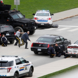 In a country that rarely sees gun violence, police officers take cover near Parliament Hill after a Canadian soldier was fatally shot Wednesday at the Canadian War Memorial in Ottawa.