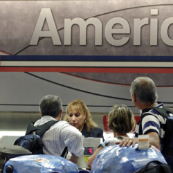 Passengers check in at Miami International Airport in Miami. American Airlines had a record profit of $942 million in the third quarter, as recent mergers have reduced competition.