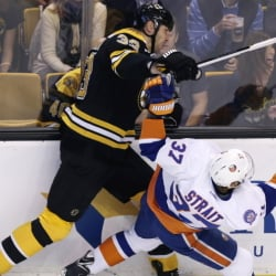 The Islanders' Brian Strait, right, collides with Bruins' defenseman Zdeno Chara during the first period Thursday. Chara left the game after a collision later in the period and will miss at least four weeks with a torn ligament.