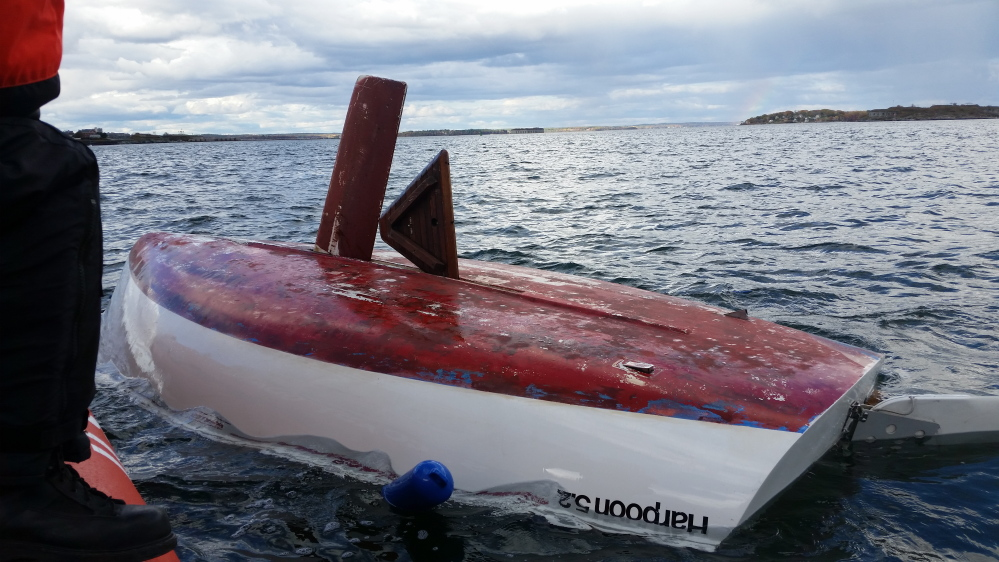 U.S. Coast Guard rescues three people from a capsized sailboat in the Portland Harbor Sunday afternoon.