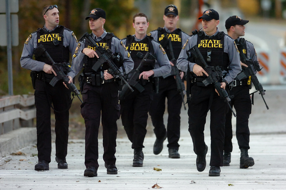 Pennsylvania State Police troopers walk along Route 191 after searching woods in Henryville, Pa., on Monday during the  manhunt for suspected killer Eric Frein. Police said late Thursday that they have Eric Frein in custody.