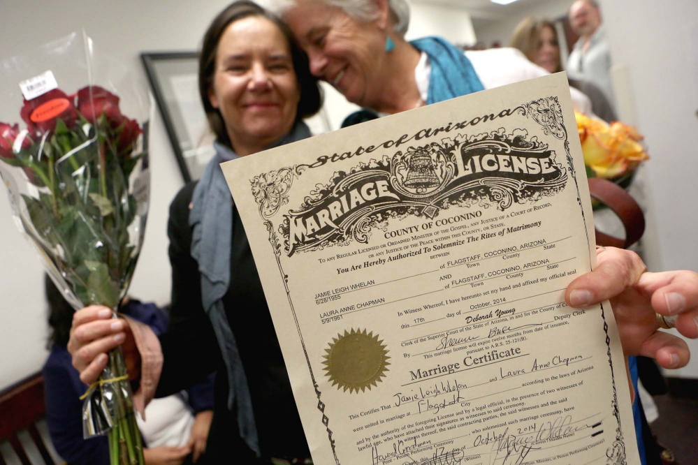 Laura Anne Chapman, left, and Jamie Whelan hold up their signed marriage certificate Oct. 17 in Flagstaff, Ariz., after becoming the second couple to be legally married in Coconino County.  AP