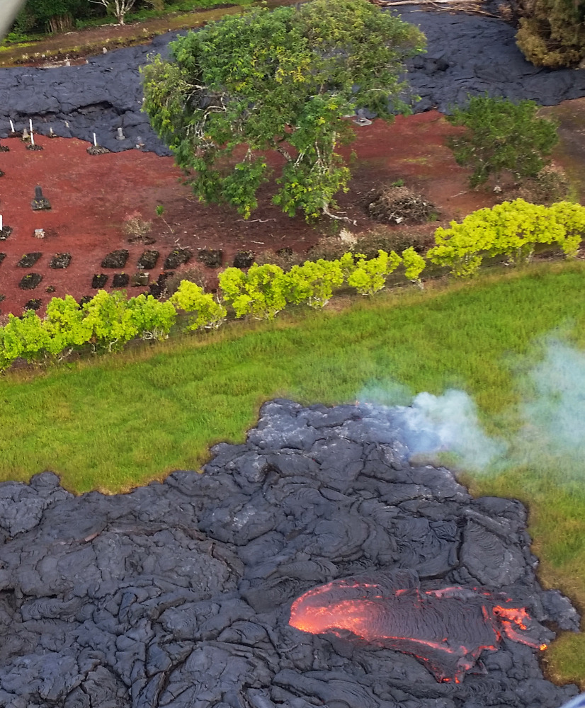 Lava partially covers a cemetery near the town of Pahoa on the Big Island of Hawaii. The lava is crawling toward a major road, threatening to further isolate the community.