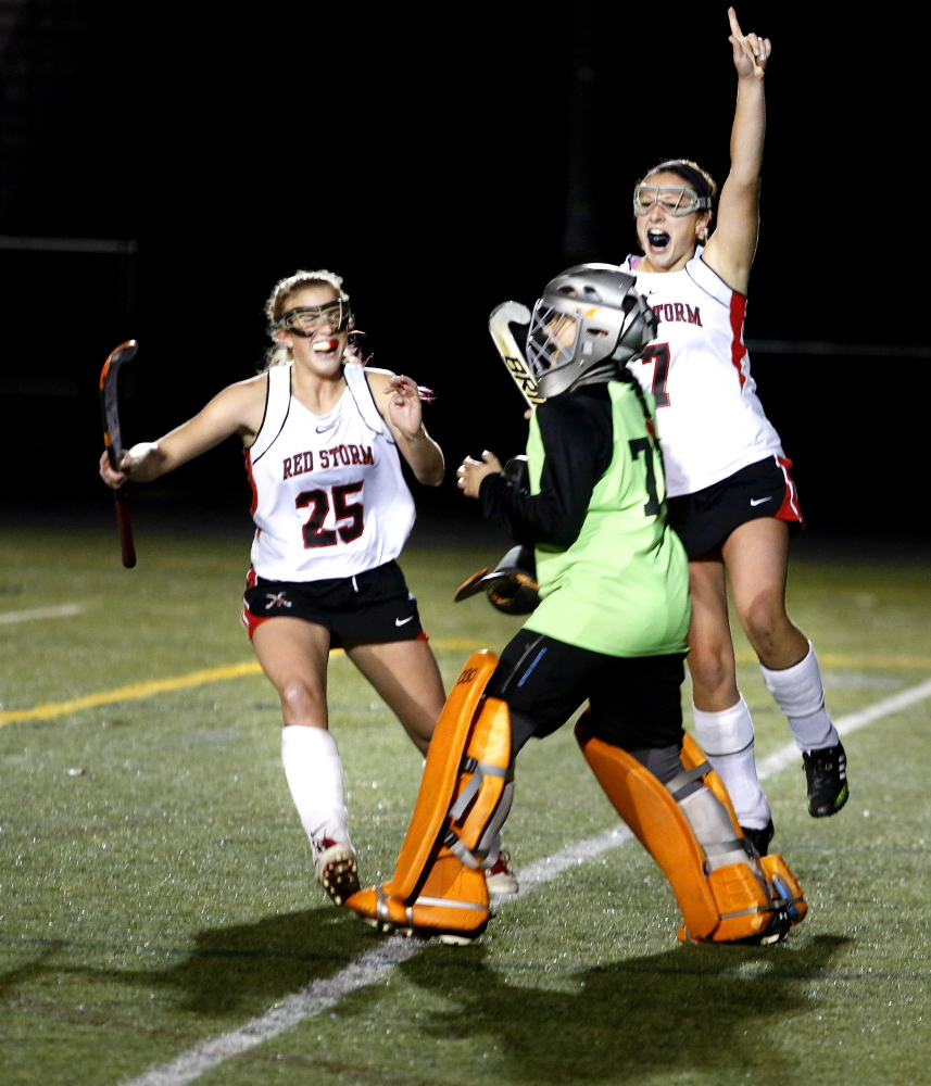 Scarborough teammates Kaitlin Prince, left, and Rose Kirsch, right, celebrate with goaltender Alyssa Souza after defeating Marshwood in the Class A Field Hockey Regional Championship Thursday.