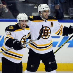 The Boston Bruins' Brad Marchand (63) celebrates his game-winning goal in overtime with teammate Patrice Bergeron on Thursday night in Buffalo, N.Y.