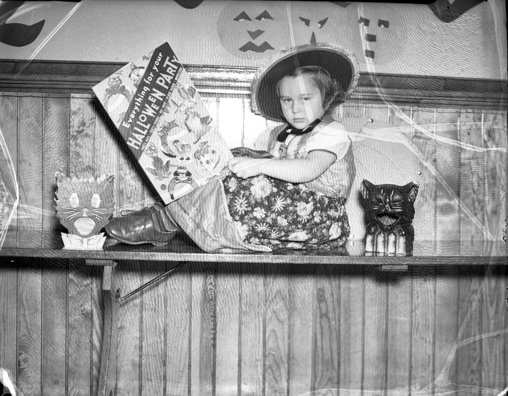 "Uncredited photo from the Oct. 27, 1937 Evening Express.  Original caption: ""Elaine Stevens [of the Longfellow School sub-primary class], just a bit perplexed with all the many Halloween suggestions, decides to study a book on the matter of 'giving a party.'"""