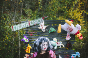 Annie Belfance waits for people to enter the Midway section of the Field of Screams at the Old Orchard Ballpark. The haunted attraction has a carnival theme this year.