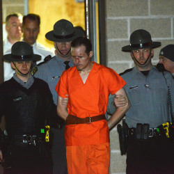 State troopers escort Eric Matthew Frein from the Blooming Grove barracks early Friday. Frein was arrested Thursday night after a 48-day manhunt. The Associated Press / The Scranton Times & Tribune