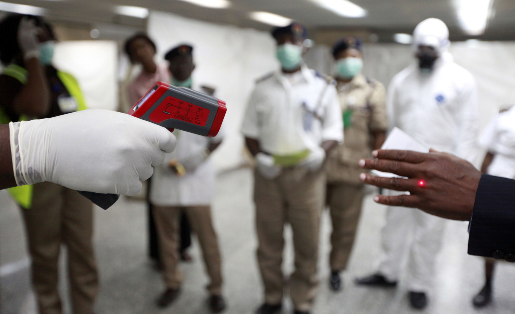 A Nigerian health official uses a thermometer on a worker at the arrivals hall of Murtala Muhammed International Airport in Lagos, Nigeria, in this Aug. 4, 2014, photo. The Associated Press