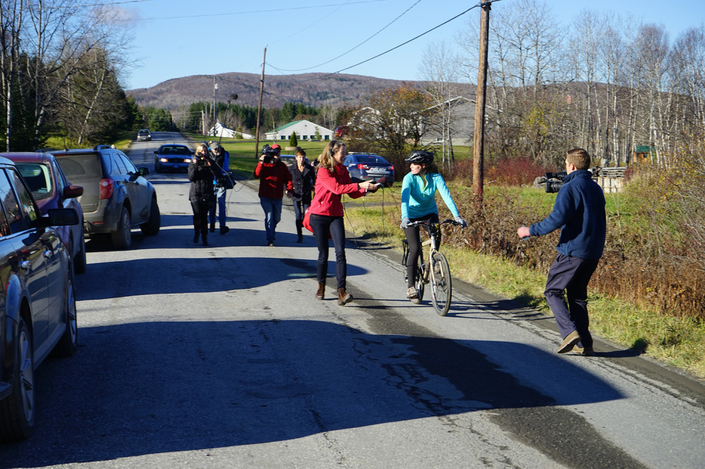 Members of the media follow Kaci Hickox Thursday as she rides bike along a road in Fort Kent.