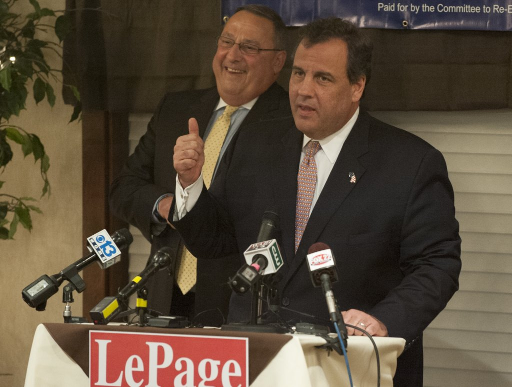 "Maine Gov. Paul LePage listens as New Jersey Gov. Chris Christie gives a campaign speech for him during a rally at the Bangor Banquet and Conference Center on Tuesday. Christie told more than 200 supporters, ""Paul LePage governs from the heart."""