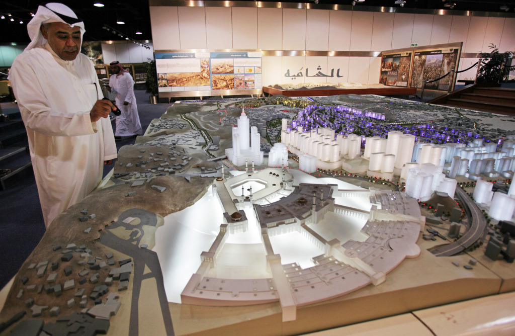 In this photo taken May 11, 2014, Essam Kalthoum, left, managing director of the Bawabat Makkah Company, which oversees several projects around Mecca, shows a prototype of what the heart of Mecca will look like after construction around the Grand Mosque is complete. The Associated Press