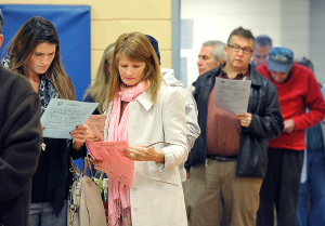 The bear-hunting debate brought Elisabeth Harding (in white coat) out to vote. She studies a sample ballot before voting at the Boys and Girls Club in South Portland.