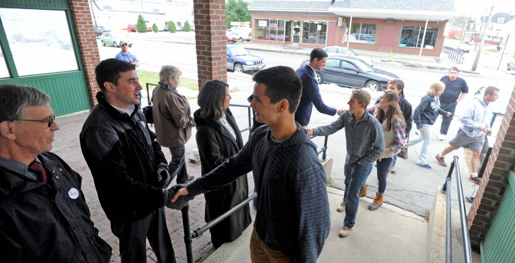 Local candidates shake hands with voters as they enter the American Legion on College Avenue in Waterville on Tuesday.