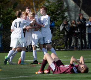 Yarmouth players swarm around Patrick Grant after Grant scored the games only goal during the state championship in Soccer.