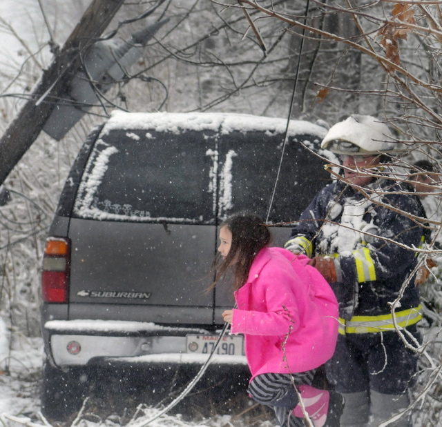 Farmingdale Assistant Fire Chief Mike LaPlante escorts Ella Cotnoir, 8, beneath power lines that trapped her family Sunday in their SUV on Maple Street in Farmingdale for over an hour. Central Maine Power shut off the power and Farmingdale firefighters got the Cotnoir family out. The West Gardiner family members, who were returning from church, were uninjured.