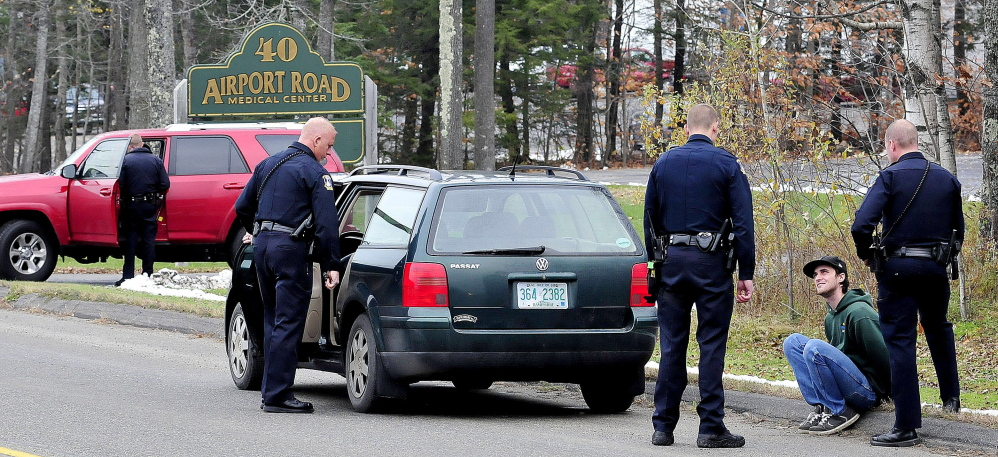 Joseph Ciampa is interviewed by Waterville police as an officer searches a car on Airport Road on Wednesday.  David Leaming / Waterville Sentinel Staff Photographer
