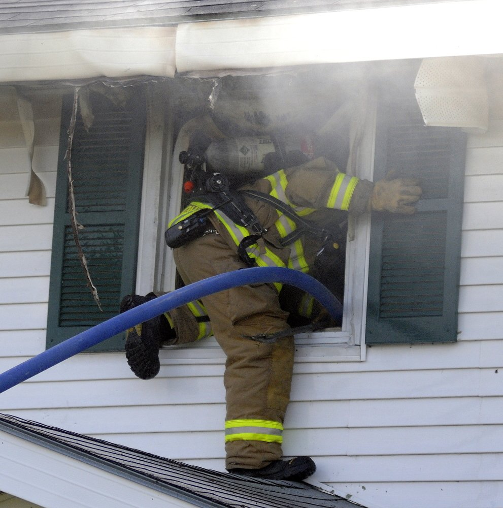A firefighter climbs through a second floor window Sunday into a residence that caught fire in Gardiner. Crews from several area communities responded to the blaze that caused extensive interior damage, according to firefighters. No injuries were reported. Andy Molloy / Kennebec Journal Staff Photographer