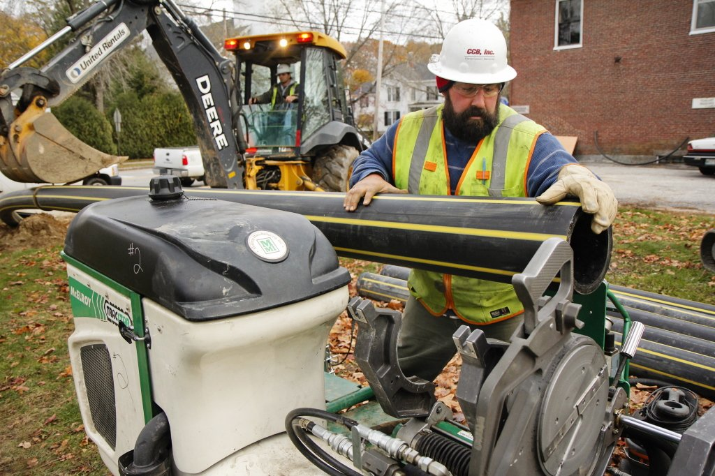 Josh Trenholm of CCB Construction of Westbrook places lengths of natural gas pipe together and fuses them with heat before pulling the pipeline underground along Main Street in Yarmouth on Friday.