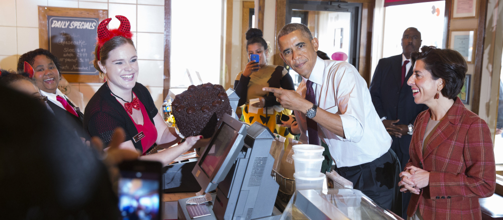 """President Obama points to a """"Death by Chocolate"""" cake he ordered Friday at Gregg's Restaurant and Pub in Providence, R.I. At right is Rhode Island Democratic gubernatorial candidate Gina Raimondo."""