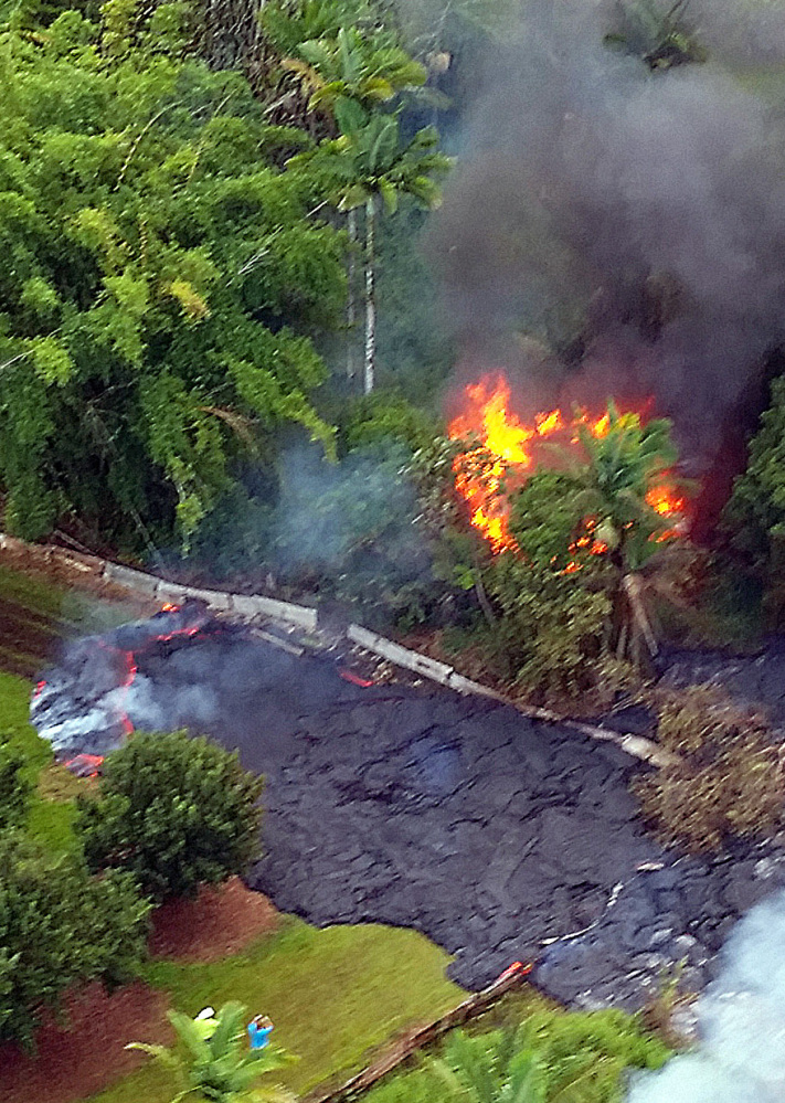 A structure burns as lava flows around it near the town of Pahoa, Hawaii, on Tuesday.