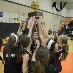 Cape Elizabeth players hoist the Gold Ball after overcoming a two-game deficit to beat Falmouth in the Class A volleyball state championship match Saturday at Biddeford High.