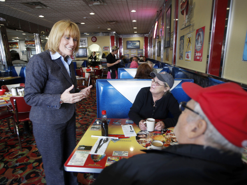 New Hampshire Gov. Maggie Hassan, a Democrat, talks with Mary and Rick Silva during a campaign stop at MaryAnn's Diner in Derry, N.H. The name recognition hat comes with being the incumbent is a plus for her campaign.