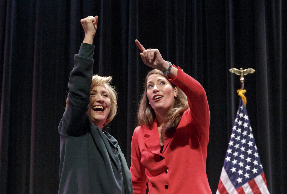 Hillary Rodham Clinton appears with Alison Lundergan Grimes on Saturday. Clinton cited equal pay for women and emphasized women's reproductive rights at a campaign event for Grimes, who is trying to unseat Kentucky Sen. Mitch McConnell.