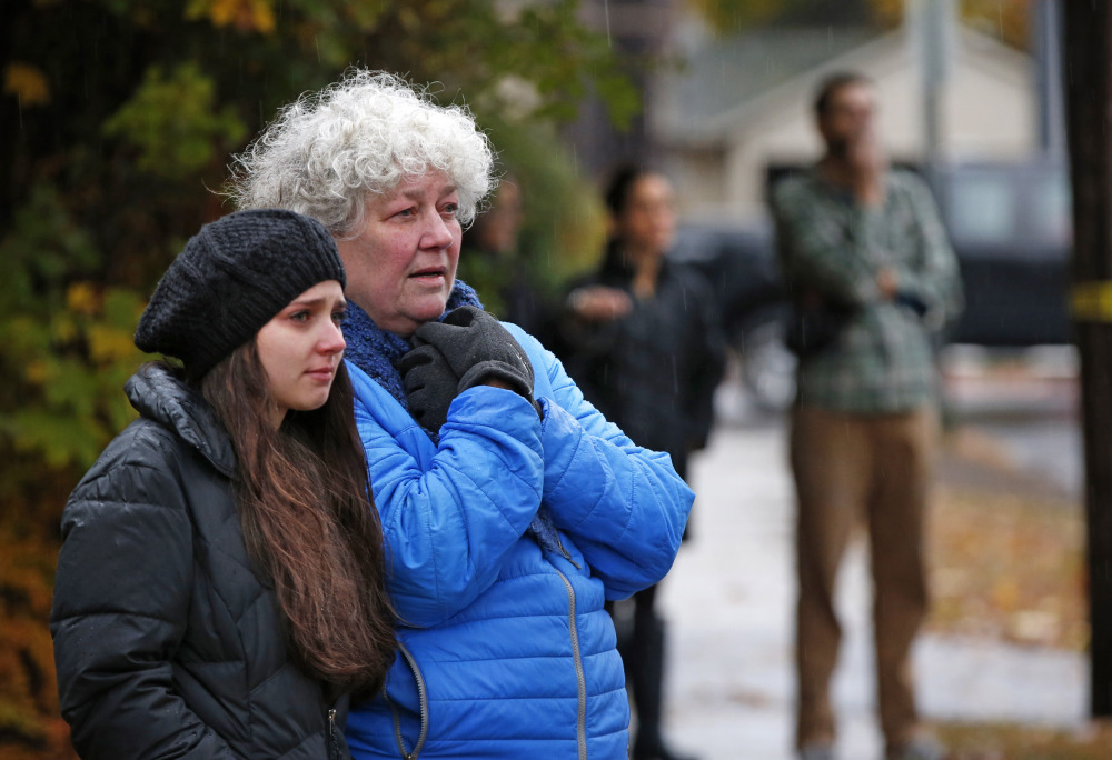 Neighbors watch as a body is removed from the scene of a fatal apartment building fire in Portland, Maine on Saturday, Nov. 1, 2014. Earlier in the morning, a fatal fire swept through a two-apartment building housing students from the University of Southern Maine. (AP Photo/Robert F. Bukaty)