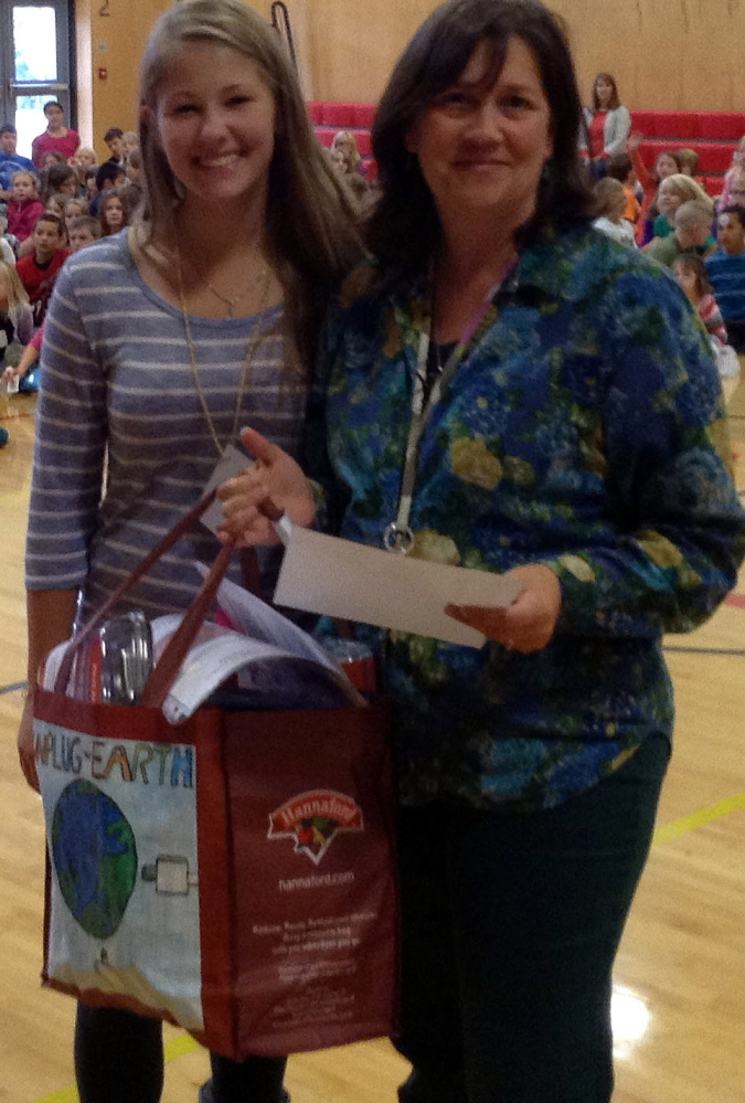 Teacher Lynn McPherson, right, receives a bag of carbon monoxide detectors from Wells High School INTERACT Club member Anna Furness at the Wells Elementary School. The Wells Beach Hose Co. donated 354 carbon monoxide detectors to students and their families.