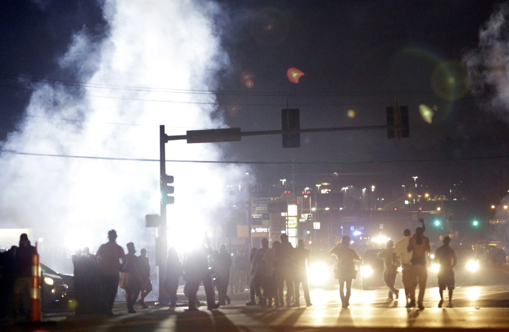 In this Aug. 18 file photo, people stand near a cloud of tear gas in Ferguson, Mo., during protests for the Aug. 9 shooting of unarmed black 18-year-old Michael Brown by a white police officer. The U.S. government agreed to a police request to shut down several miles of airspace surrounding Ferguson, even though authorities said their purpose was to keep media helicopters away during protests in August, according to recordings of air traffic control conversations obtained by The Associated Press.