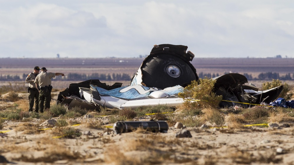 Law enforcement officers take a closer look at the wreckage near the site where a Virgin Galactic space tourism rocket, SpaceShipTwo, exploded and crashed in Mojave, Calif. Saturday.