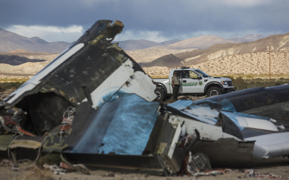 Law enforcement officers stand watch Saturday near the wreckage of SpaceShipTwo, a Virgin Galactic space tourism rocket that had exploded and crashed in Mojave, Calif. a day earlier, killing one of the pilots aboard.