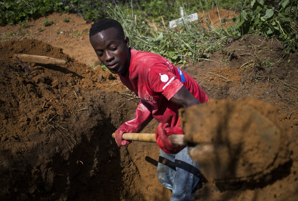 A member of a hospital burial team digs a grave for a child who had died of Ebola earlier that day in Ganta, Liberia. Awareness has improved, but experts fear some victims will avoid treatment centers and disappear into remote areas.