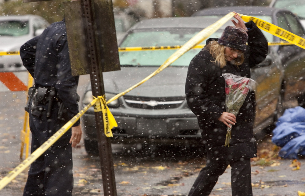 A police officer assists a woman preparing to add flowers to a growing memorial for the fire victims. The woman would not give her name, but said she knew a girl who died in the fire.