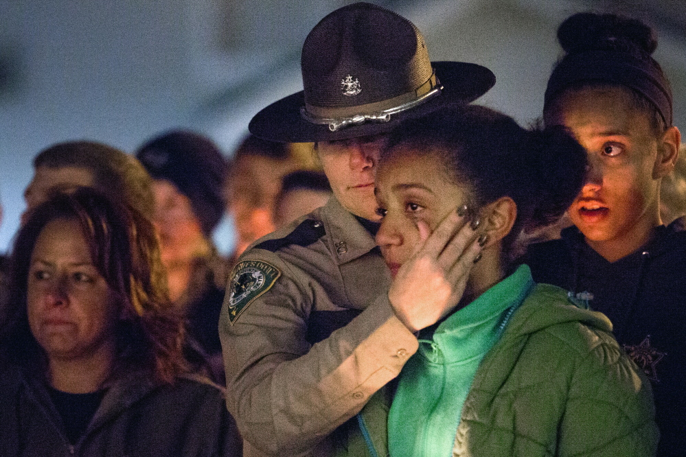 CORNISH, ME - NOVEMBER 3: Deputy Christina McAllister with the Oxford County Sheriff's Department wipes tears away from the face of her daughter, Viktoria Sugars, 11, as McAllister's other daughter, Cayla Sugars, 14, looks on, during a vigil at Call's Shop 'n Save on Route 25 in Cornish Monday evening, November 3, 2014, for the victims of a car crash that killed two teenagers in Hiram early Saturday morning. Andrew Stanley, 18, of Porter, died at the scene, and Isaac Moore, 19, of Parsonsfield, died at Maine Medical Center. McAllister is the school resource officer at Sacopee Valley High School where both of the victims graduated from. (Photo by Gabe Souza/Staff Photographer)