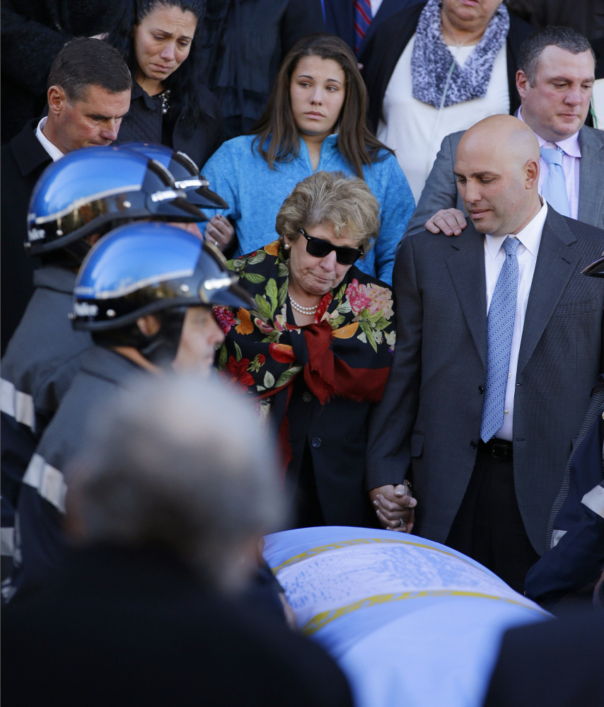 "Angela Menino, center, stands behind the casket of her late husband, former Boston mayor Tom Menino, outside a Boston church as the song ""My Way"" is sung after Menino's funeral Mass. His successor called him a 'relentless, big-hearted, people-loving urban mechanic."""