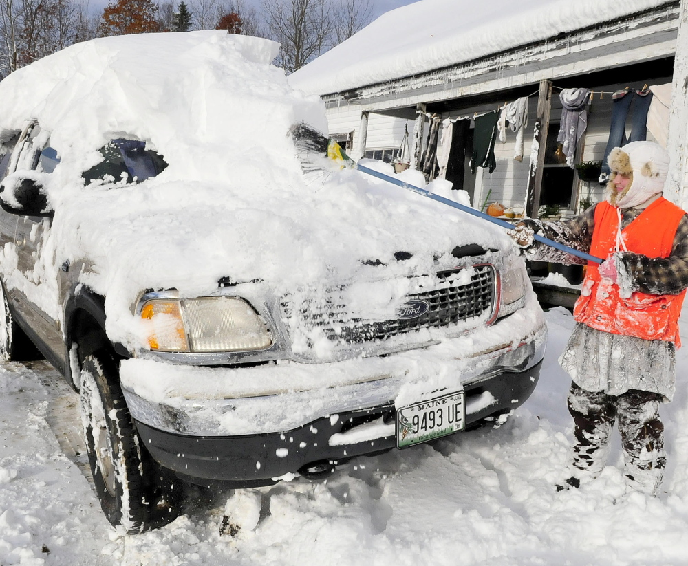 NOV. 3: Sydney Astbury uses a broom Monday to clear the nearly foot of snow that buried the family vehicle at her home in Troy. Many towns near Troy were without power as wind and heavy snow hit the area Sunday.