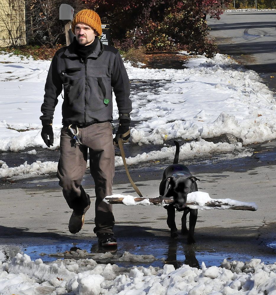 Timothy Wing walks his dog Ruby, who has a good hold on a snow-covered stick in Waterville on Monday.