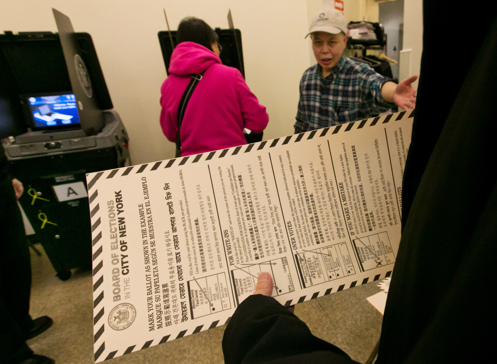 A voter carries her ballot Tuesday to be scanned at a polling place in New York's Chinatown neighborhood.