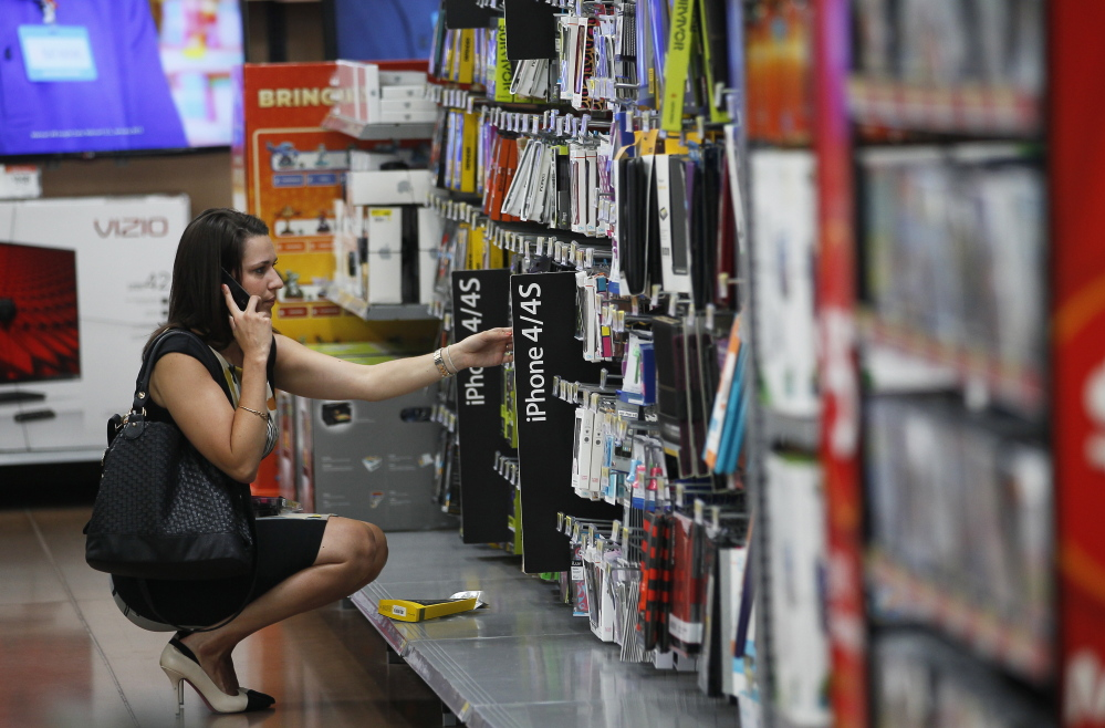 A woman shops at a Wal-Mart Supercenter in Rogers, Ark. While each product is offered to all customers for the same price in this and other brick-and-mortar stores, prices for the same item can vary per user online.